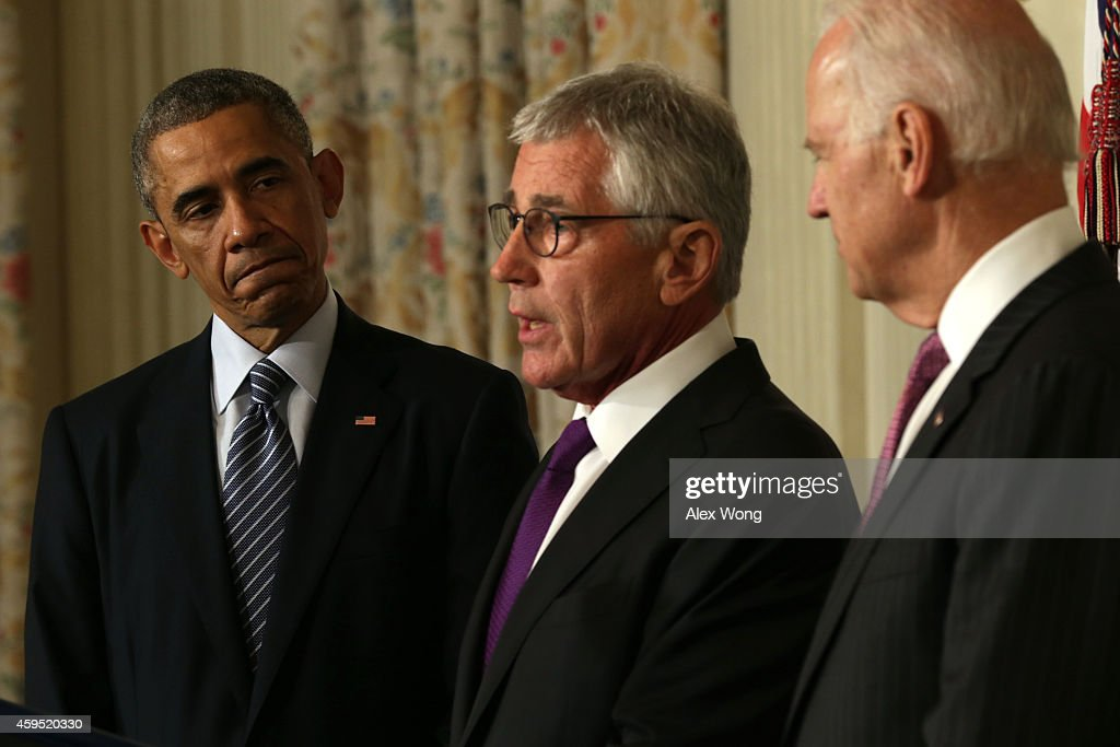 U.S. Secretary of Defense Chuck Hagel (C) speaks as President Barack Obama (L) and Vice President Joe Biden look on during a press conference announcing Hagel's resignation in the State Dining Room of the White House November 24, 2014 in Washington, DC. Sources say Hagel plans to remain in office until his successor is confirmed by the Senate.