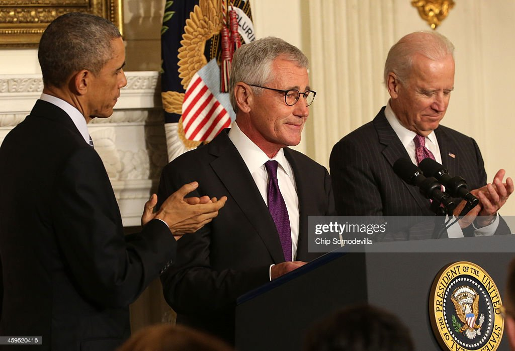 U.S. Secretary of Defense <a gi-track='captionPersonalityLinkClicked' href=/galleries/search?phrase=Chuck+Hagel&family=editorial&specificpeople=504963 ng-click='$event.stopPropagation()'>Chuck Hagel</a> (C) speaks as President <a gi-track='captionPersonalityLinkClicked' href=/galleries/search?phrase=Barack+Obama&family=editorial&specificpeople=203260 ng-click='$event.stopPropagation()'>Barack Obama</a> (L) and Vice President Joe Biden look on during a press conference announcing Hagel's resignation in the State Dining Room of the White House November 24, 2014 in Washington, DC. Sources say Hagel plans to remain in office until his successor is confirmed by the Senate.