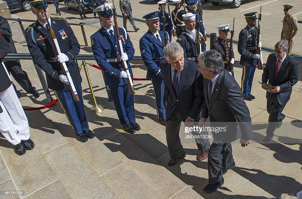 US Secretary of Defense Chuck Hagel (C) talks with Portugal's Minister of National Defense Jose Pedro Aguiar-Branco (R) during an honor cordon at the Pentagon in Washington, DC, March 31, 2014. AFP PHOTO / Jim WATSON