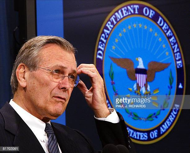 Secretary of Defense Donald H Rumsfeld pauses as he calls on a reporter as he stands in front of the Department of Defense logo while conducting his...