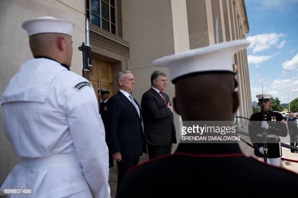 US Secretary of Defense James Mattis and Ukraine's President Petro Poroshenko listen to the Ukrainian national anthem outside the Pentagon on June 20...