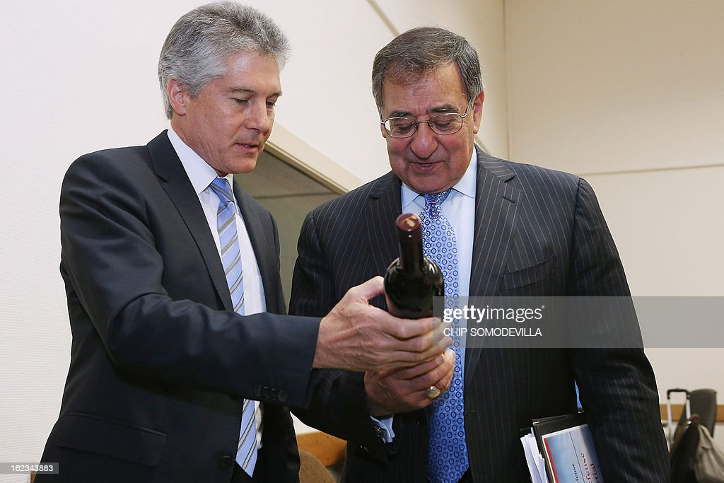 US Secretary of Defense Leon Panetta (R) and Australian Defense Minister Stephen Smith exchange gifts of wine before a meeting during the North Atlantic Treaty Organization (NATO) Defense Ministers Meetings at NATO headquarters on February 22, 2013 in Brussels, Belgium. Panetta is attending meetings and holding bilateral meetings with other NATO defense officials.