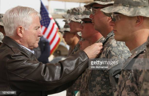 S Secretary of Defense Robert Gates pins medals on US soldiers while visiting Forward Operating Base HowzEMadad in Kandahar Province December 8 2010...