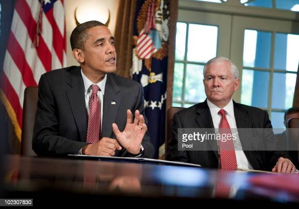 Secretary of Defense Robert M Gates listens as President Barack Obama speaks to the press after a meeting in the Cabinet Room of the White House June...