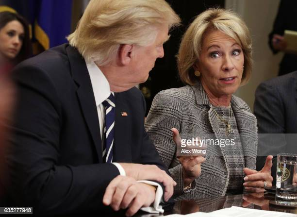 S Secretary of Education Betsy DeVos speaks as President Donald Trump listens during a parentteacher conference listening session at the Roosevelt...