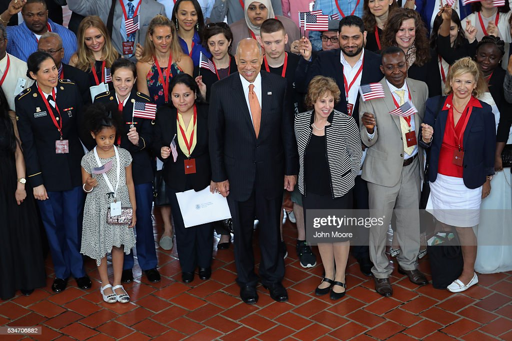 U.S. Secretary of Homeland Security <a gi-track='captionPersonalityLinkClicked' href=/galleries/search?phrase=Jeh+Johnson&family=editorial&specificpeople=5862084 ng-click='$event.stopPropagation()'>Jeh Johnson</a> (C), poses for photos with new American citizens in the Great Hall of Ellis Island following a naturalization ceremony on May 27, 2016 in New York City. Johnson administered the oath of citizenship to immigrants from 39 countries on the historic island in New York Harbor where millions of immigrants were first processed upon arrival to America.