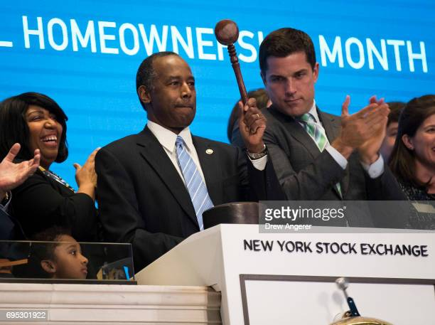 S Secretary of Housing and Urban Development Ben Carson flanked by wife Candy Carson and Thomas Farley president of the NYSE bangs the gavel after...