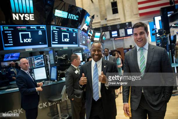 US Secretary of Housing and Urban Development Ben Carson gives the thumbs up as he walks with Thomas Farley president of the NYSE as he tours the...