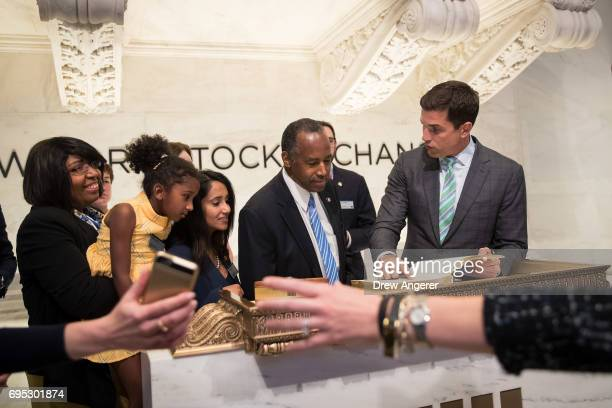S Secretary of Housing and Urban Development Ben Carson signs a guest book on the the floor of the New York Stock Exchange before ringing the closing...