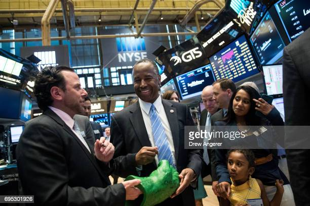 S Secretary of Housing and Urban Development Ben Carson signs an autograph for a trader as he tours the floor of the New York Stock Exchange after...