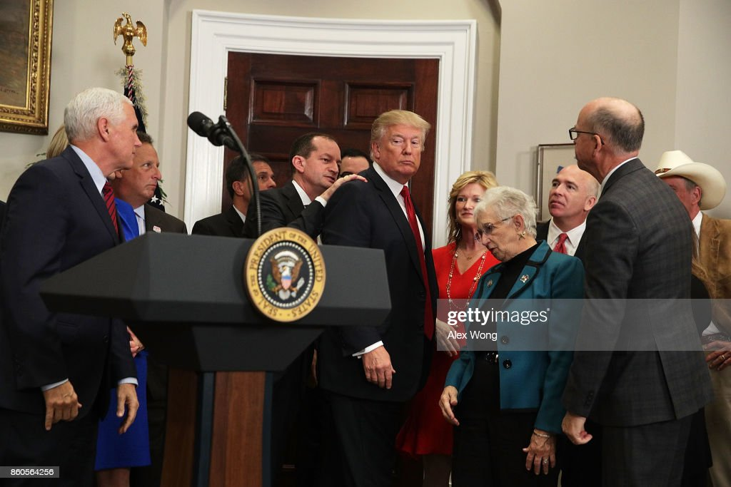 U.S. Secretary of Labor Alexander Acosta taps on the shoulder of U.S. President Donald Trump to remind him to sign an executive order after his remarks as Vice President Mike Pence (L) looks on in the Roosevelt Room of the White House October 12, 2017 in Washington, DC. President Trump signed the executive order to loosen restrictions on Affordable Care Act 'to promote healthcare choice and competition.'