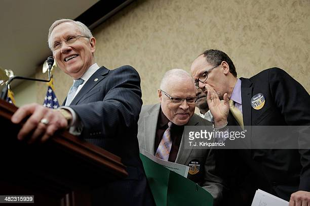 Secretary of Labor Thomas Perez right talks with Lee Saunders president of AFSCME as Senate Majority Leader Harry Reid speaks during a stop of the...