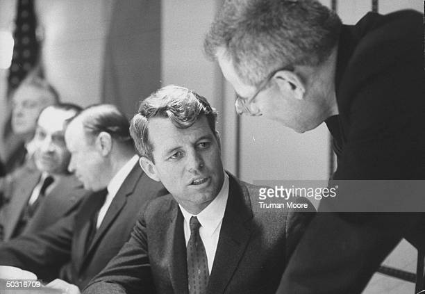 Secretary of Labor W Willard Wirtz speaking with Attorney General Robert F Kennedy at meeting of fund for the Republic's Center for study of...