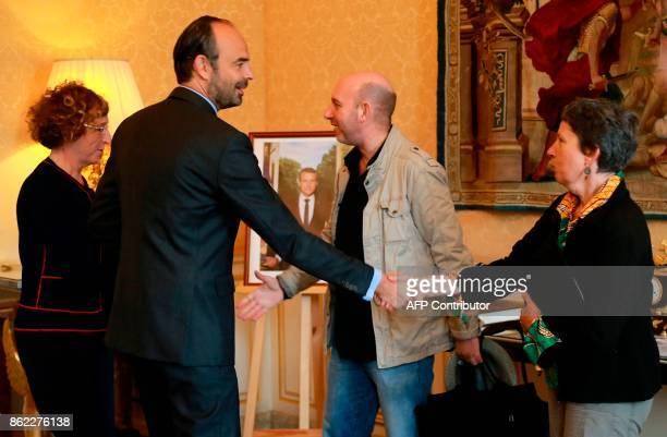 Secretary of National Union of Syndicale Solidaires Caroline Angeli shakes hands with French Prime Minister Edouard Philippe as Union spokesman Eric...
