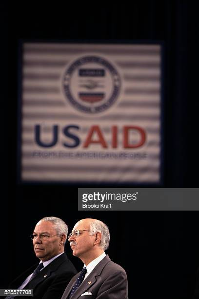 US Secretary of State Colin Powell and US AID Administrator Andrew Natsios listen as President George W Bush speaks to USAID and NGO personnel in...