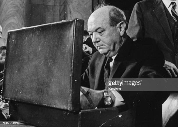 US Secretary of State Dean Rusk pictured using his briefcase as he prepares to answer questions about the Vietnam War in front of the US Senate circa...