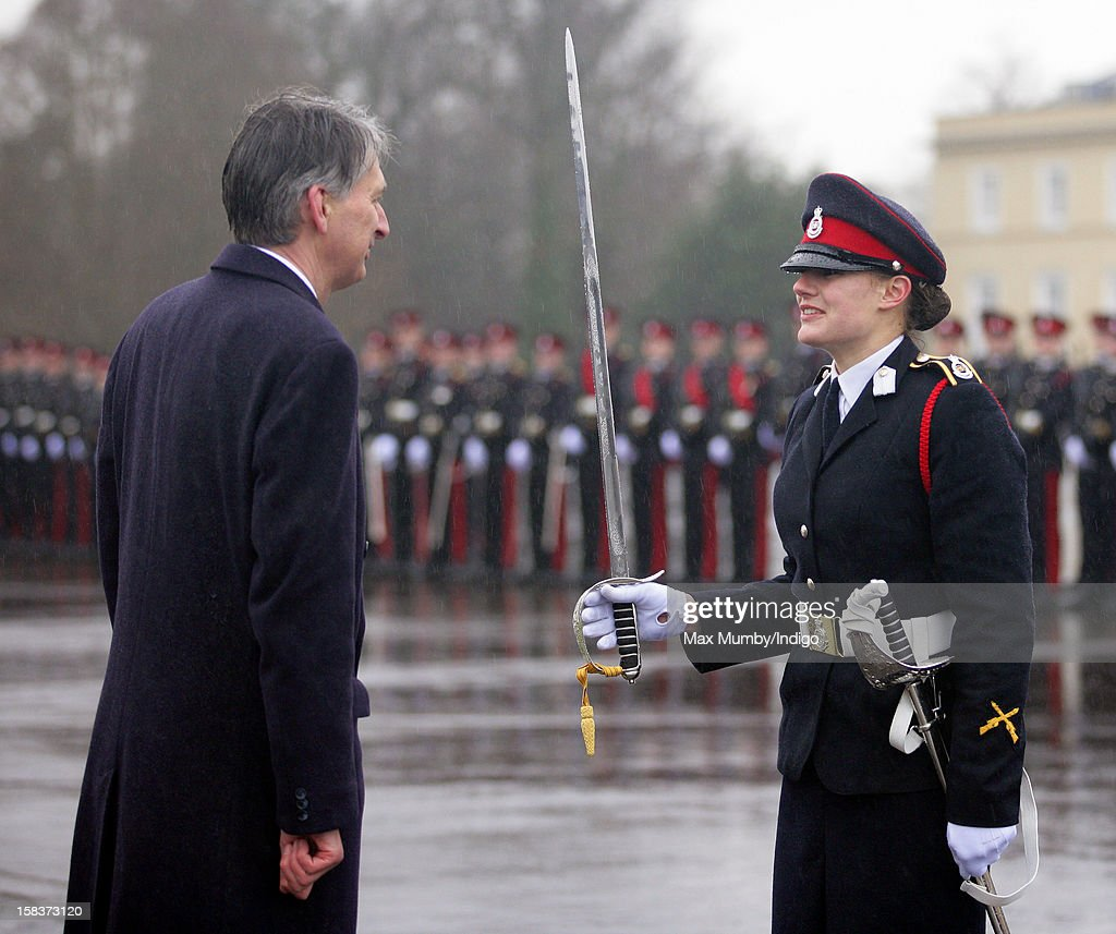 Secretary of State for Defence <a gi-track='captionPersonalityLinkClicked' href=/galleries/search?phrase=Philip+Hammond&family=editorial&specificpeople=2486715 ng-click='$event.stopPropagation()'>Philip Hammond</a> presents Senior Under Officer Sarah Hunter-Choat with the Sword of Honour whilst representing Queen Elizabeth II during the Sovereign's Parade at the Royal Military Academy Sandhurst on December 14, 2012 in Sandhurst, England. The parade marks the completion of 44 weeks of training for 200 young people who will be commissioned into the British Army and the armies of 13 overseas countries. Senior Under Officer Sarah Hunter-Choat became the fourth woman in the Royal Military Academy's history to receive the prestigious Sword of Honour which is awarded to the best Officer Cadet on the course.