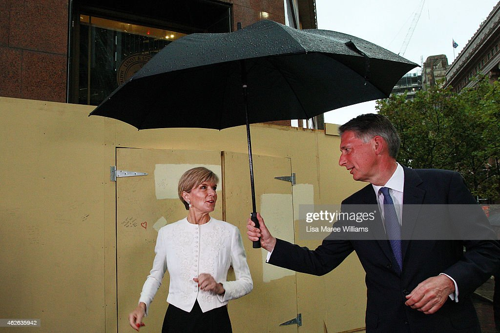 UK Secretary of State for Foreign and Commonwealth Affairs, Philip Hammond holds a umbrella above Australian Minister for Foreign Affairs, Julie Bishop, at the Lindt Cafe Siege site at Martin Place on February 2, 2015 in Sydney, Australia. On December 15 2014, gunman Man Haron Monis was shot dead by police after taking hostages at the Lindt Chocolat Cafe in Martin Place. Two other people died, 33-year-old cafe manager Tori Johnson and 38-year-old Sydney barrister Katrina Dawson.