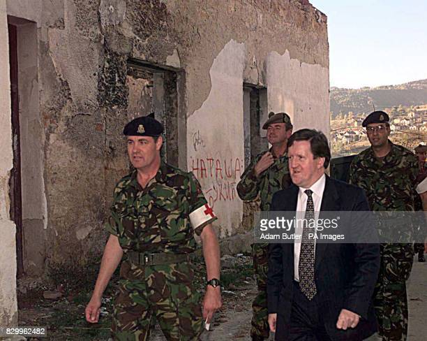 Secretary of State George Robertson walks through a war battered area of the Bosnian town of Sipovo today where the British military are currently...