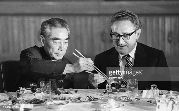 US Secretary of State Henry Kissinger accepts food from Chinese Premier Zhou Enlai during a state banquet in the Great Hall of the People in Beijing