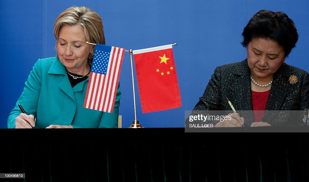 Secretary of State Hillary Clinton and Chinese State Councilor Liu Yandong (R) sign the US-China Consultation on People-to-People Exchange agreement at the National Center for the Performing Arts in Beijing on May 25, 2010. The United States and China were wrapping up strategic talks aimed at smoothing out differences on currency and trade issues, as Washington presses Beijing to get tough on North Korea. AFP PHOTO / POOL / Saul LOEB