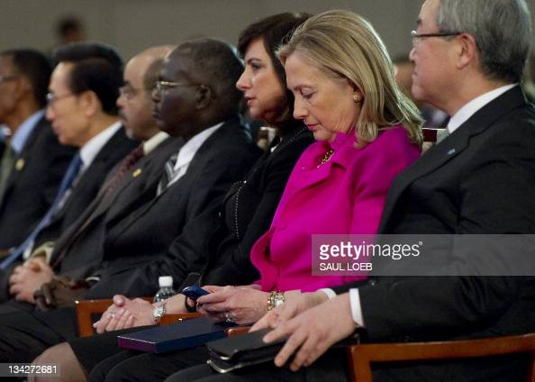 US Secretary of State Hillary Clinton checks her Blackberry phone alongside Korean Foreign Minister Kim Sunghwan as she attends the Fourth High Level...