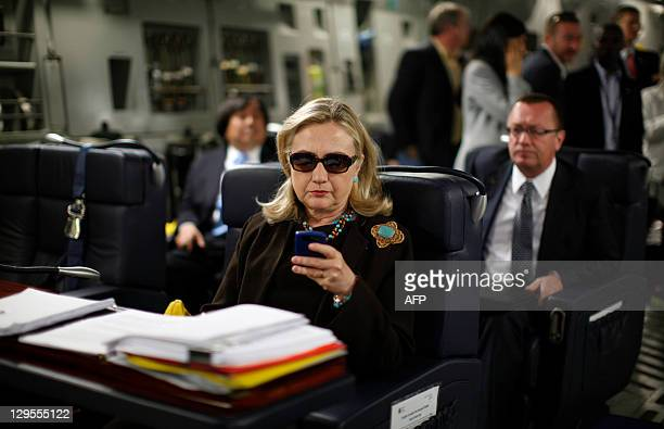 US Secretary of State Hillary Clinton checks her PDA upon departure in a military C17 plane from Malta bound for Tripoli on October 18 2011 AFP...