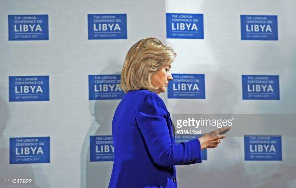S Secretary of State Hillary Clinton checks her phone at the opening of the Libyan Conference a meeting of international allies to discuss the next...