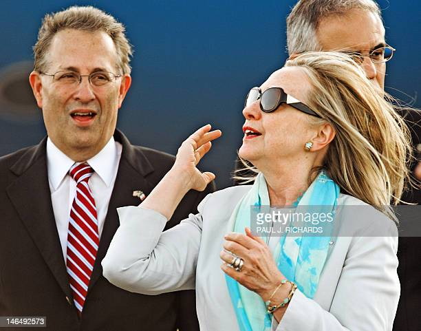 US Secretary of State Hillary Clinton flips her hair standing next to an unidentified official after she stepped off her official airplane June 17...