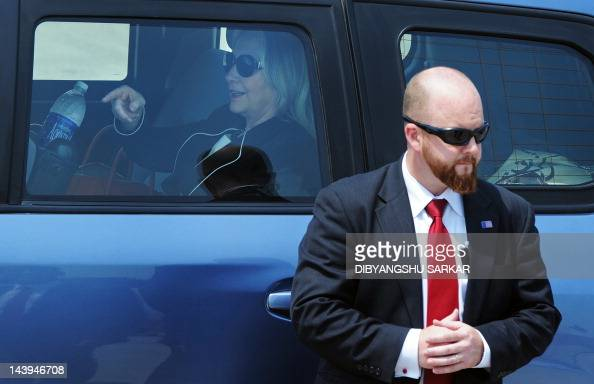 US Secretary of State Hillary Clinton gestures inside her vehicle as a Secret Service agent keeps watch following her arrival at the Netaji Subhash...