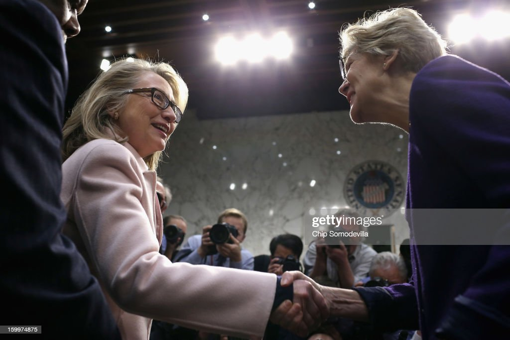 U.S. Secretary of State Hillary Clinton (L) greets Sen. Elizabeth Warren (D-MA) as they arrive for Sen. John Kerry's (D-MA) confirmation hearing before the Senate Foreign Relations Committee to become the next Secretary of State in the Hart Senate Office Building on Capitol Hill January 24, 2013 in Washington, DC. Nominated by President Barack Obama to succeed Hillary Clinton as Secretary of State, Kerry has served on this committee for 28 years and has been chairman for four of those years.