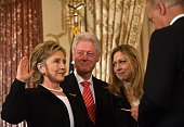 US Secretary of State Hillary Clinton is ceremonially sworn in by Vice President Joe Biden as her husband former president Bill Clinton and daughter...