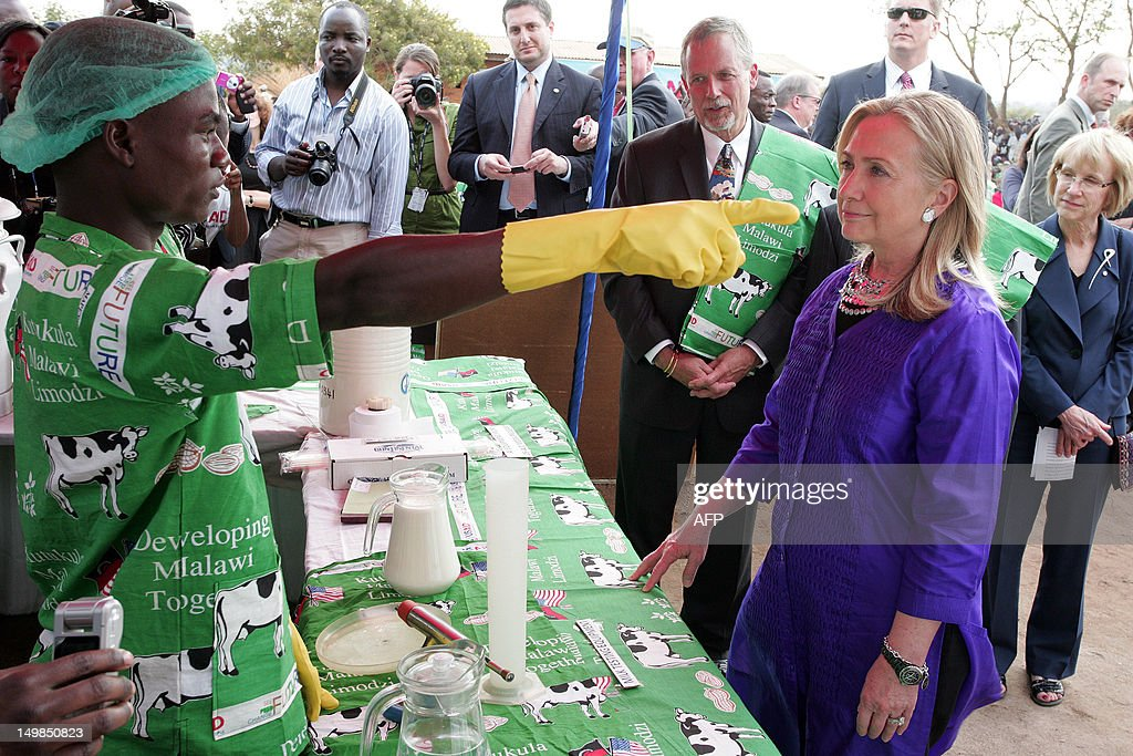US Secretary of State <a gi-track='captionPersonalityLinkClicked' href=/galleries/search?phrase=Hillary+Clinton&family=editorial&specificpeople=76480 ng-click='$event.stopPropagation()'>Hillary Clinton</a> (R) listens to a milk laboratory tester at the Lumbadzi Milk Bulking Group on August 5, 2012 in Lilongwe, Malawi. Clinton became the first US chief diplomat to visit Malawi where she 'encouraged President Banda to be a role model in Southern Africa for more democratic governance and also regional integration among the states of this region.'.
