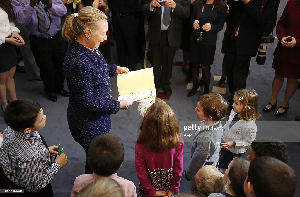US Secretary of State Hillary Clinton (C) looks at a book given to her by Irish and American children during a visit to the US Embassy in Dublin, Ireland, on December 6, 2012. US Secretary of State Hillary Clinton on Thursday issued a sharp warning to European and central Asian nations that some countries were backsliding on democratic values and human rights. AFP PHOTO / KEVIN LAMARQUE/POOL