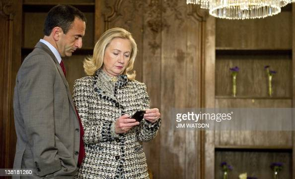 US Secretary of State Hillary Clinton looks at a phone message with Assistant Secretary of State for European Affairs Philip Gordon as they wait in a...
