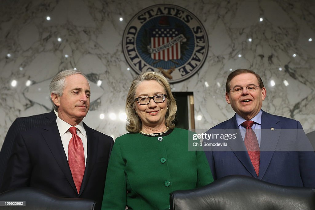 U.S. Secretary of State Hillary Clinton (C) poses for photographs with Senate Foreign Relations Committee ranking member Sen. Bob Corker (R-TN) (L) and Chairman Robert Menendez (D-NJ) before a hearing with the Senate Foreign Relations Committee on Capitol Hill January 23, 2013 in Washington, DC. Lawmakers questioned Clinton about the security failures during the September 11 attacks against the U.S. mission in Benghazi, Libya, that led to the death of four Americans, including U.S. Ambassador Christopher Stevens.