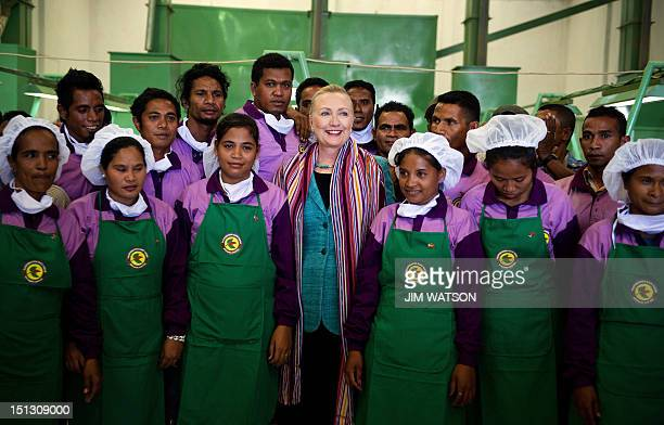 US Secretary of State Hillary Clinton poses with workers during a tour of the Timor Coffee Cooperative in Dili on September 6 2012 Clinton is paying...