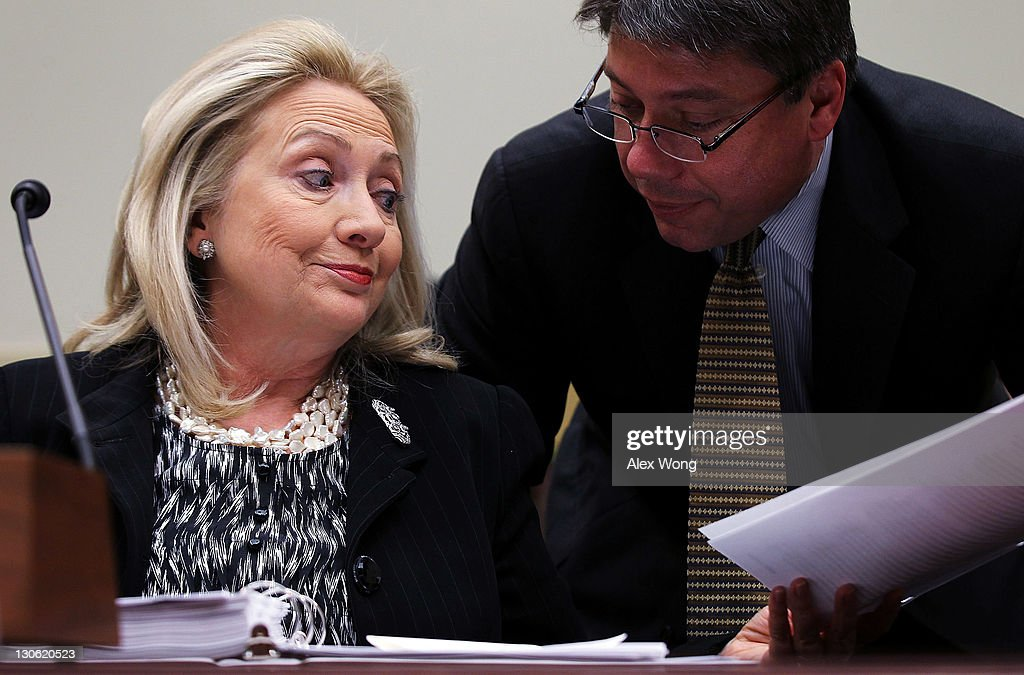 U.S. Secretary of State <a gi-track='captionPersonalityLinkClicked' href=/galleries/search?phrase=Hillary+Clinton&family=editorial&specificpeople=76480 ng-click='$event.stopPropagation()'>Hillary Clinton</a> (L) reacts as she listens to an aide during a hearing before the House Foreign Affairs Committee October 27, 2011 on Capitol Hill in Washington, DC. Clinton testified on 'Afghanistan and Pakistan: Transition and the Way Forward.'