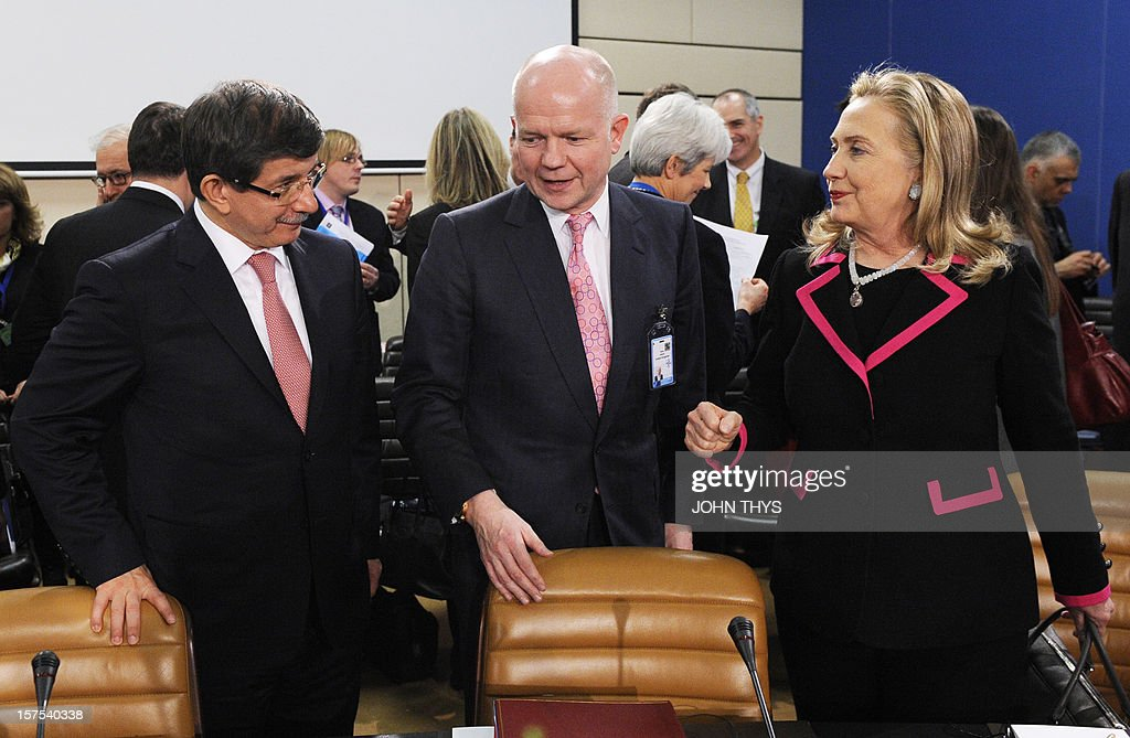 US Secretary of State Hillary Clinton (R) reacts while speaking with Britain's Secretary of State for Foreign and Commonwealth Affairs William Hague (C) and Turkey's Foreign Minister Ahmet Davutoglu (L) during a meeting of foreign affairs ministers from the 28 North Atlantic Treaty Organization (NATO) member-countries to discuss Syria and Turkey's request for Patriot missiles to be deployed protectively on the Turkish-Syrian border at the NATO Headquarters in Brussels, on December 4, 2012.