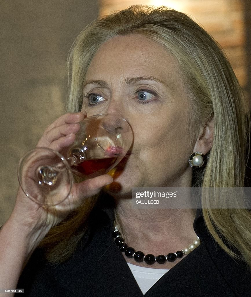 US Secretary of State Hillary Clinton samples wine in a wine cellar prior to dinnerat Adjarian Wine House in Batumi on June 5, 2012. AFP PHOTO / POOL / Saul LOEB