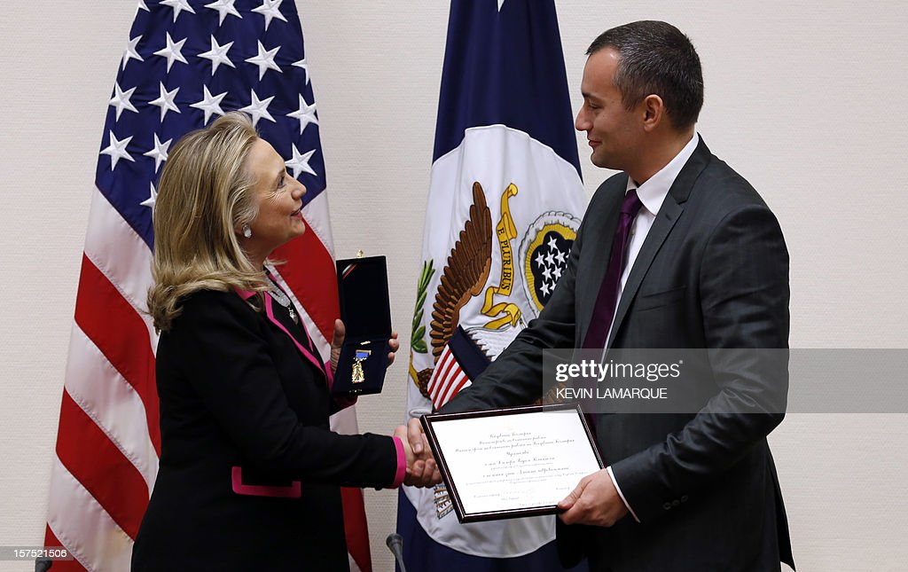 US Secretary of State Hillary Clinton (L) shakes hands with Bulgarian Foreign Minister Nickolay Mladenov as she is given a medal during their meeting at the NATO headquarters in Brussels December 4, 2012. AFP PHOTO / POOL / Kevin Lamarque