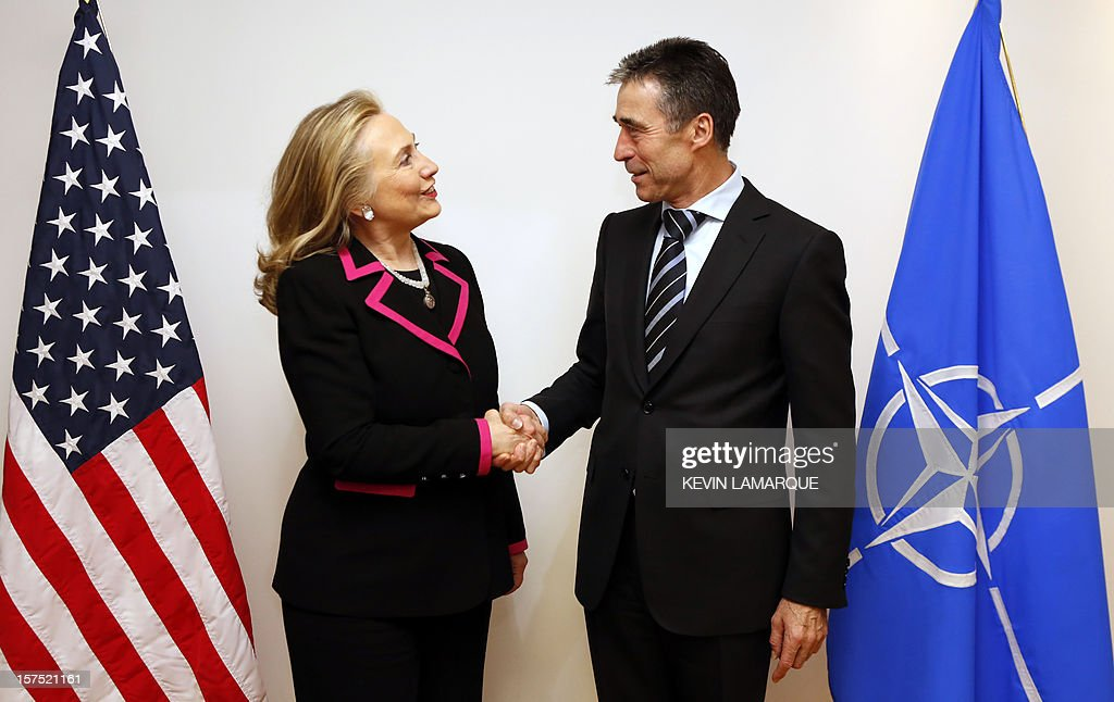 US Secretary of State Hillary Clinton (L) shakes hands with North Atlantic Treaty Organization (NATO) Secretary-General Anders Fogh Rasmussen on December 4, 2012 before a meeting of foreign ministers from the 28 NATO member-countries at organization headquarters in Brussels to discuss Syria and Turkey's request for Patriot missiles to be deployed protectively on the Turkish-Syrian border. . AFP PHOTO / POOL / KEVIN LAMARQUE