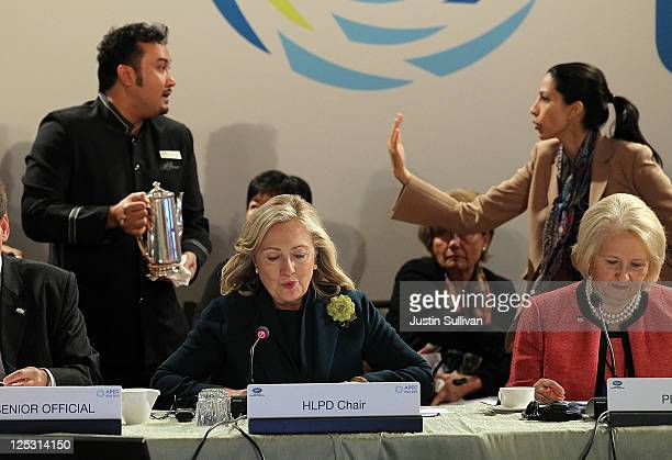 S Secretary of State Hillary Clinton speaks during a roundtable discussion as her deputy chief of staff Huma Abedin tells a coffee server to move out...