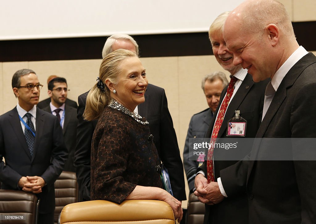 US Secretary of State Hillary Clinton (L) speaks with British Foreign Secretary William Hague (R) on December 5, 2012 at a meeting with Non-NATO ISAF contributing countries on the second and last day of talks between foreign ministers from the 28 North Atlantic Treaty Organization (NATO) member countries at organization headquarters in Brussels. NATO ministers are to discuss Syria as well as Afghanistan, Russia-NATO ties and the situation in Georgia and the Balkans. AFP PHOTO / POOL / KEVIN LAMARQUE