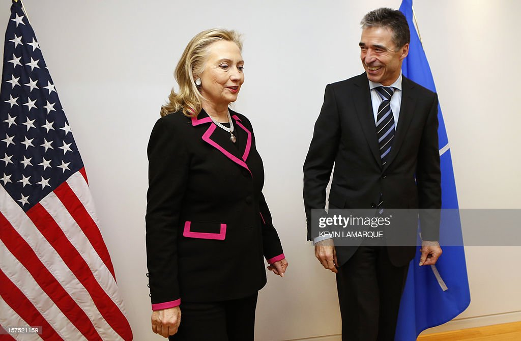 US Secretary of State Hillary Clinton (L) speaks with North Atlantic Treaty Organization (NATO) Secretary-General Anders Fogh Rasmussen on December 4, 2012 before a meeting of foreign ministers from the 28 NATO member-countries at organization headquarters in Brussels to discuss Syria and Turkey's request for Patriot missiles to be deployed protectively on the Turkish-Syrian border. . AFP PHOTO / POOL / KEVIN LAMARQUE