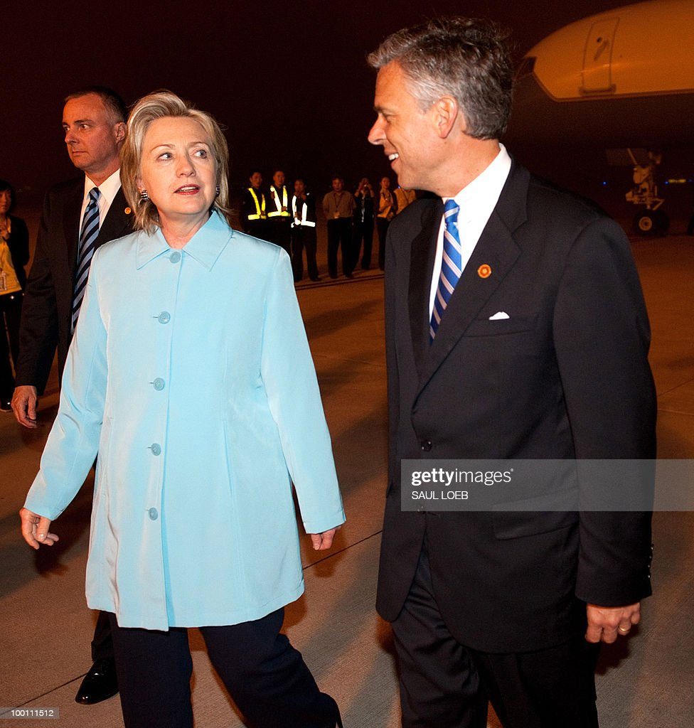 US Secretary of State Hillary Clinton (L) speaks with US Ambassador to China Jon Huntsman (R) after arriving at Pudong International Airport in Shanghai on May 21, 2010. Clinton and her Japanese counterpart condemned North Korea, a day after a multinational panel blamed it for a deadly torpedo attack on a South Korean warship. AFP PHOTO/POOL/Saul LOEB