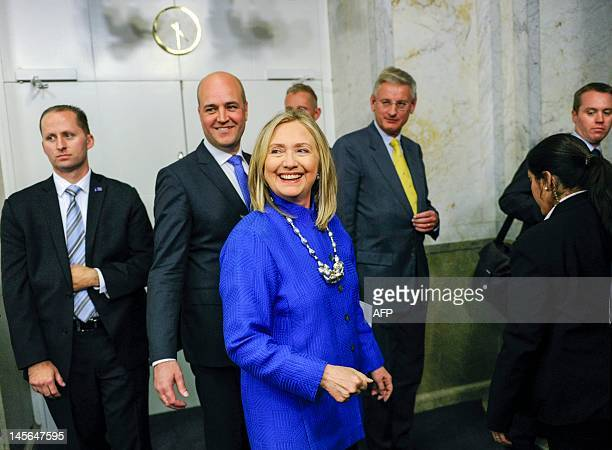 US Secretary of State Hillary Clinton surrounded by Sweden's Prime Minister Fredrik Reinfeldt and Foreign Minister Carl Bildt laughs on her way to a...