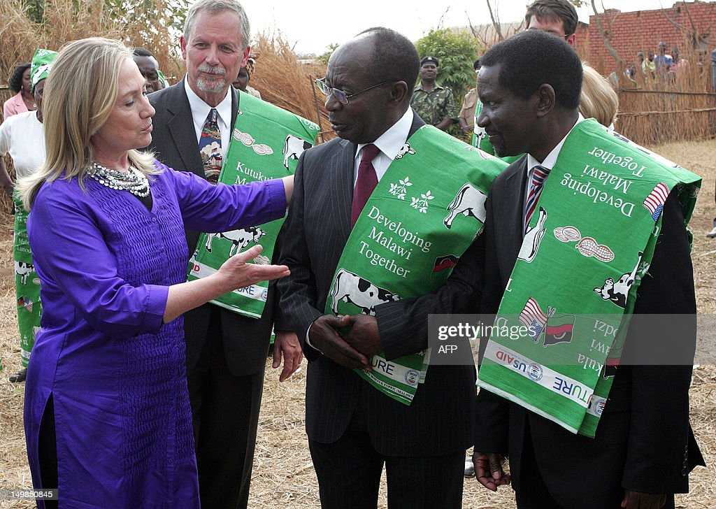 US Secretary of State Hillary Clinton talks to Malawian Minister of Agriculture Peter Mwanza (C) and Malawian Foreign Minister Ephraim Mganda Chiume (L) at the Lumbadzi Milk Bulking Group on August 5, 2012 in Lilongwe, Malawi. Clinton became the first US chief diplomat to visit Malawi where she 'encouraged President Banda to be a role model in Southern Africa for more democratic governance and also regional integration among the states of this region.'.