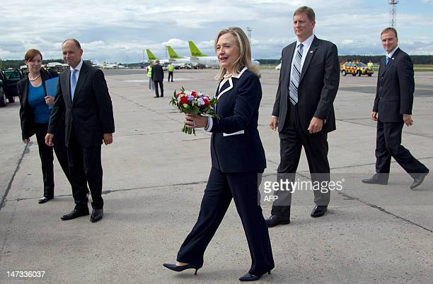 US Secretary of State Hillary Clinton walks with a bouquet of flowers she received after arriving in Riga on June 28 2012 Hillary Clinton touched...