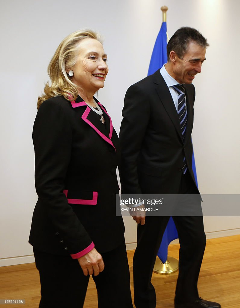 US Secretary of State Hillary Clinton (L) walks with North Atlantic Treaty Organization (NATO) Secretary-General Anders Fogh Rasmussen on December 4, 2012 before a meeting of foreign ministers from the 28 NATO member-countries at organization headquarters in Brussels to discuss Syria and Turkey's request for Patriot missiles to be deployed protectively on the Turkish-Syrian border. . AFP PHOTO / POOL / KEVIN LAMARQUE